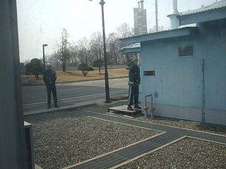 小屋脇から半身出して北朝鮮側を警戒する韓国軍兵士